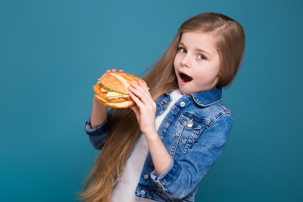 Little pretty girl in jean jacket with long brown hair hold a burger
