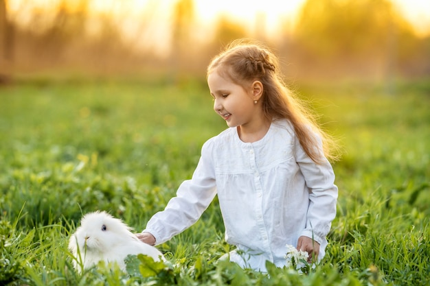 Little pretty girl petting a white rabbit on the lawn at sunset