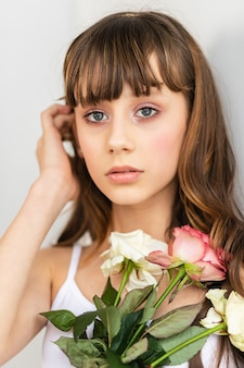 Little pretty girl in pink holds the bouquet of roses. close up the flowers and face, little ballerina with a bouquet
