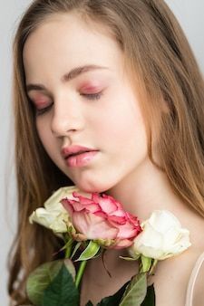 Little pretty girl in pink holds the bouquet of roses. close up the flowers and face
