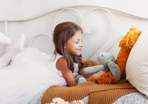 小さなかわいい女の子がぬいぐるみで寝台のベッドで遊ぶ