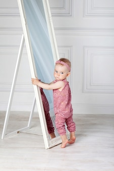 Little pretty girl plays with a big mirror