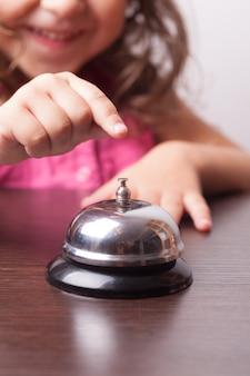 小さなかわいい女の子がベルを押す、時間通りにボードゲーム