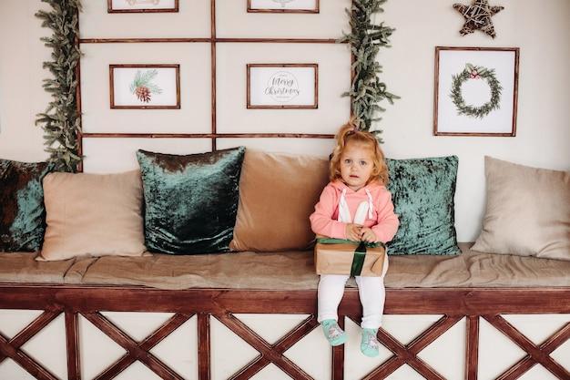 小さなかわいい女の子シス波状ハイエはプレゼント付きの箱とソファの座る