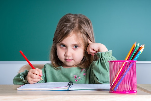 Little pretty girl sitting in the classroom at the gray desk and draws.