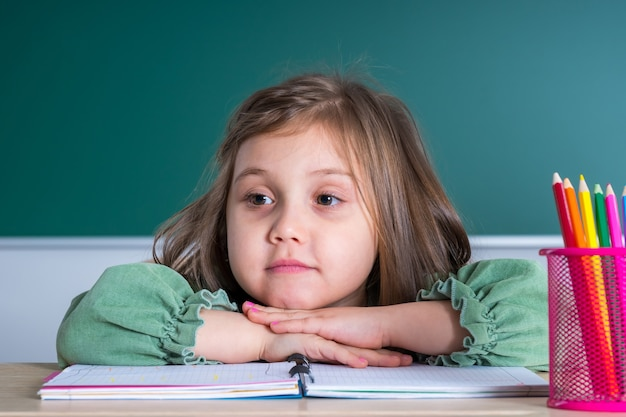 Little pretty girl sitting in the classroom at the gray desk and posing.