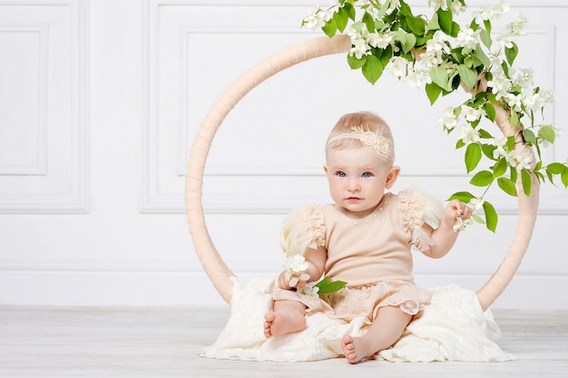 Little pretty girl with blue eyes sits on a floor with flowers of a jasmine. copy space
