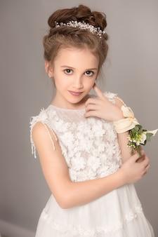 Маленькая красивая девушка с цветами, одетые в свадебные платья