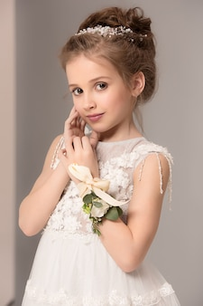 Little pretty girl with flowers dressed in wedding dresses