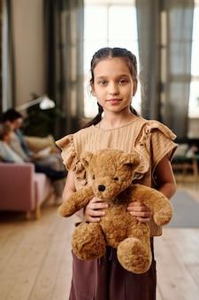 Маленькая симпатичная девочка с мягким коричневым медвежонком смотрит на вас, стоя перед камерой, против своей семьи, сидящей на диване в гостиной