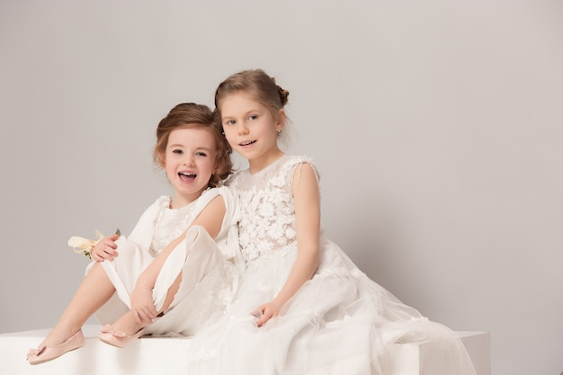 Little pretty girls with flowers dressed in wedding dresses.