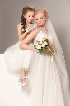 Little pretty girls with flowers dressed in wedding dresses
