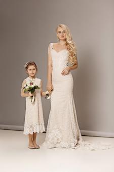 Bambine graziose con fiori vestiti in abiti da sposa