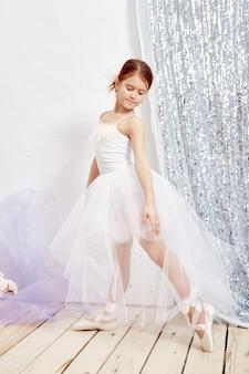 リトルプリマバレエ。若いバレリーナガールがバレエパフォーマンスの準備をしています。白い夜会服の女の子と窓の近くのポワント、美しい赤い髪。若い演劇女優