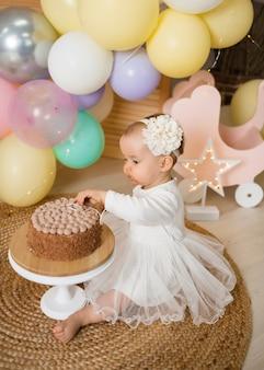 드레스와 머리띠에 작은 공주 소녀는 케이크 옆에 앉아있다