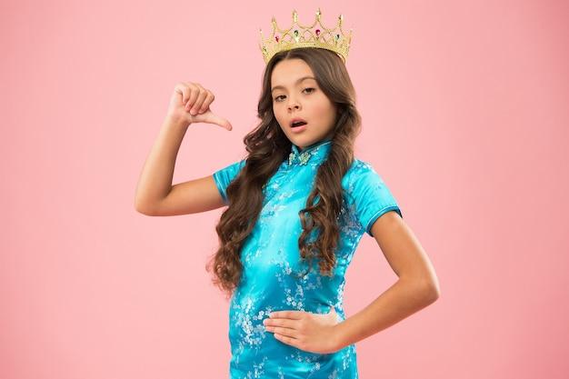 Маленькая принцесса. девушка носит корону. манеры принцессы. концепция премии. победитель конкурса красоты. международный конкурс красоты. ребенок носит золотой символ короны славы. конкурс красоты. сосредоточьтесь на красоте.