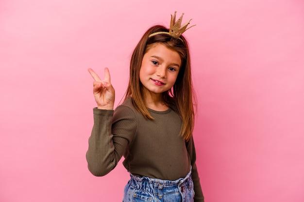 ピンクの背景に分離された王冠を持つ小さな王女の女の子は、指で平和のシンボルを示して楽しくてのんきです。