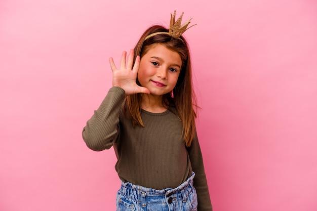 ピンクの背景に分離された王冠を持つ小さな王女の女の子は、指で5番目を示す陽気な笑顔を浮かべています。