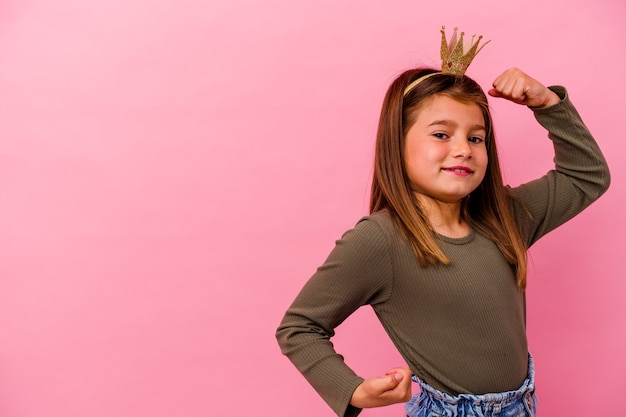 Little princess girl with crown isolated on pink background raising fist after a victory, winner concept.