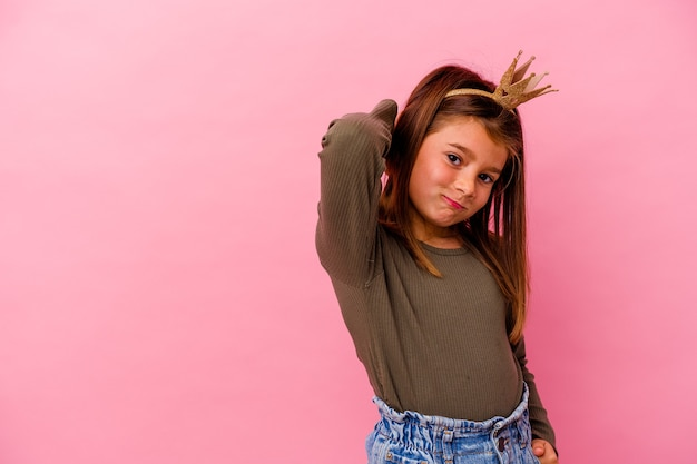 Little princess girl with crown isolated on pink background touching back of head, thinking and making a choice.