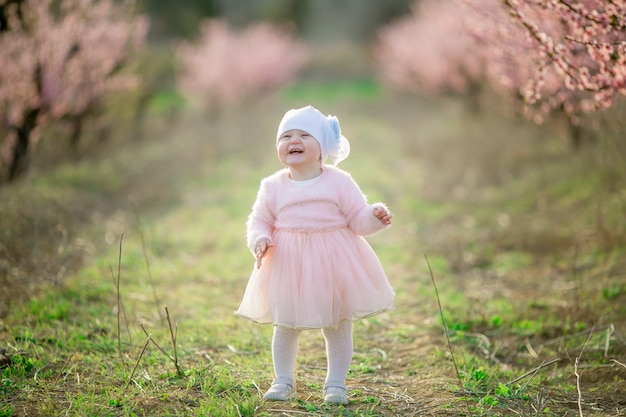 Little princess toddler dressed in a pink dress walks in the fresh air and enjoys life