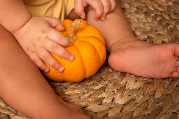 Little pumpkin in the hands of a baby. child holding a pumpkin on a straw chair