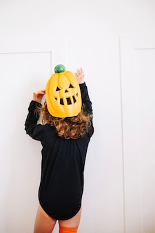 Little pumpkin looking at white wall