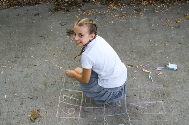 Little pupil girl play in school yard. school break during classes