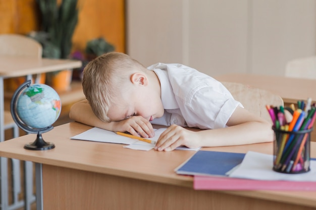 Little pupil laying on table in classroom