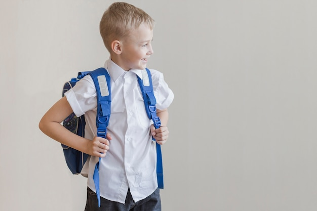 Little pupil with backpack in studio
