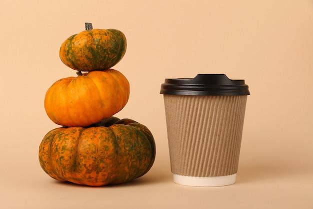 Маленькая пирамида из тыкв и чашка кофе рядом с ней. концепция острого латте. ремесло коричневые одноразовые чашки.