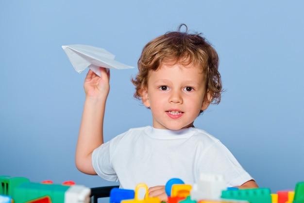 勉強する準備がほとんどできていません。子供の学校。幸せな表情の小さな男の子の生徒は、笑って笑って紙飛行機を保持します。