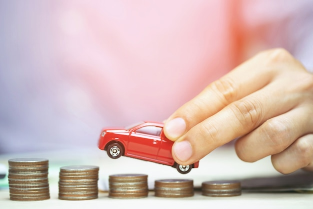 Little red car over a lot of money stacked coins for loans costs finance concept. empty copy space for text.