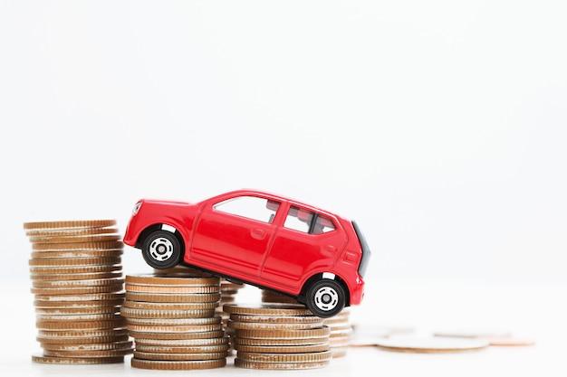 Маленькая красная машина за много денег с накоплением монет. по банковским кредитам затраты на финансирование. страхование, покупка автомобиля концепция финансирования. купить и оплатить в рассрочку авансовый платеж авто.