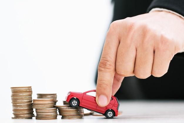 많은 돈 위에 작은 빨간 차 쌓인 동전. 대출 비용 금융 개념.