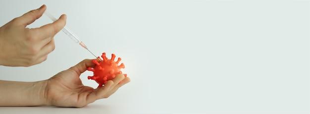 手に小さな赤いコロナウイルスモデル。予防接種プロセス。 covid 19ウイルス、ワクチン、パンデミック。コロナウイルスの背景、テキスト用の空き領域、コピー領域。