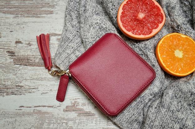 セーターの小さな赤い女性の財布と柑橘類