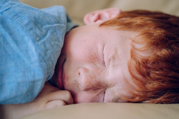 眠っている不安の問題を持つ小さな赤い髪の少年。悪夢と子供の概念の悪い夢。自宅で子供たちのライフスタイル。家族の安全保障。メガネのない小さな子供のための失明ビジョン。
