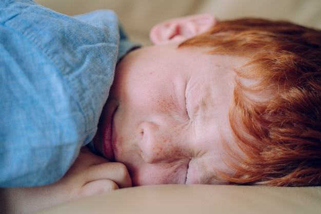 Little red hair boy with anxiety problem sleeping. nightmares and bad dreams in children concept. lifestyle with kids at home. family security. sight loss vision for small children without glasses.
