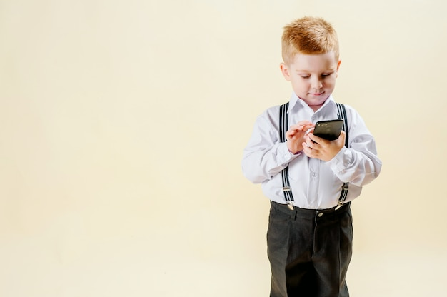 Little red-haired boy in a business suit with a phone in his hand hurries to a meeting in a business suit, business, mini boss
