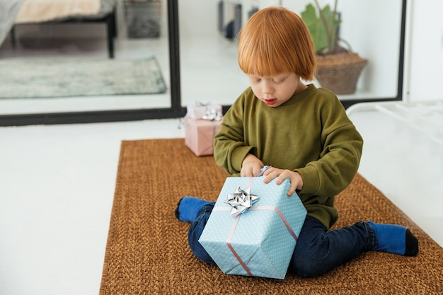 Little red haired boy unpacking christmas present