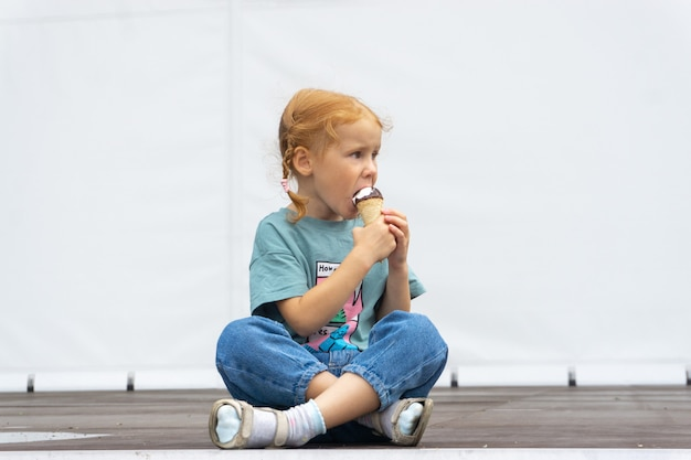 Little red-haired caucasian cute girl sitting cross-legged and eating ice cream.