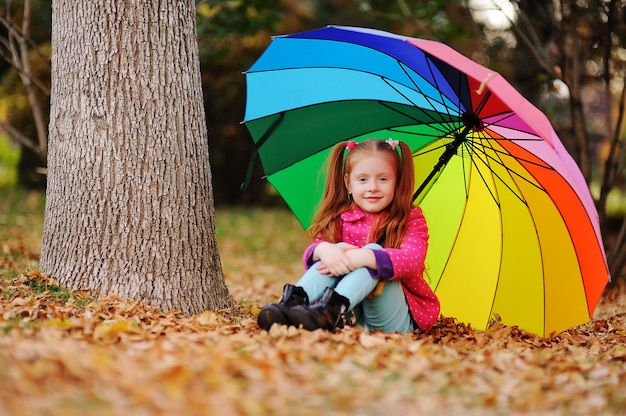 A little red-haired girl in a pink jacket sits on yellow leaves with a large umbrella of rainbow color.
