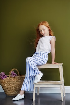 Little red-haired girl with a basket of flowers posing on an olive wall. spring portrait of a redhead girl with blue eyes. hair the color of fire, norwegian teen girl
