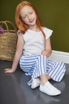 Little red-haired girl with a basket of flowers