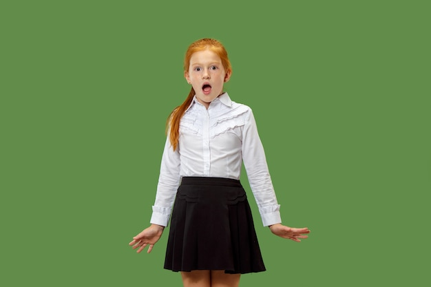 Little red-haired surprised girl isolated on green studio