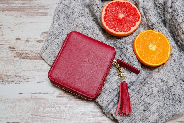 Little red lady's purse and citrus on a sweater