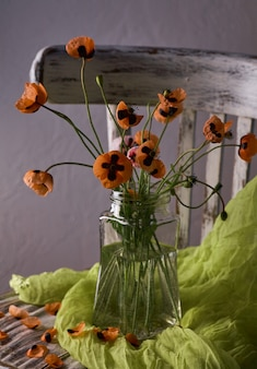 A little red poppies bouquet arranged in classical style stillife of popies in a glasses vase on vintage