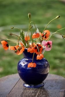 クラシックなスタイルでアレンジされた小さな赤いポピーの花束