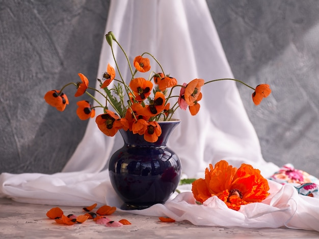 A little red poppies bouquet in blue ceramic vase